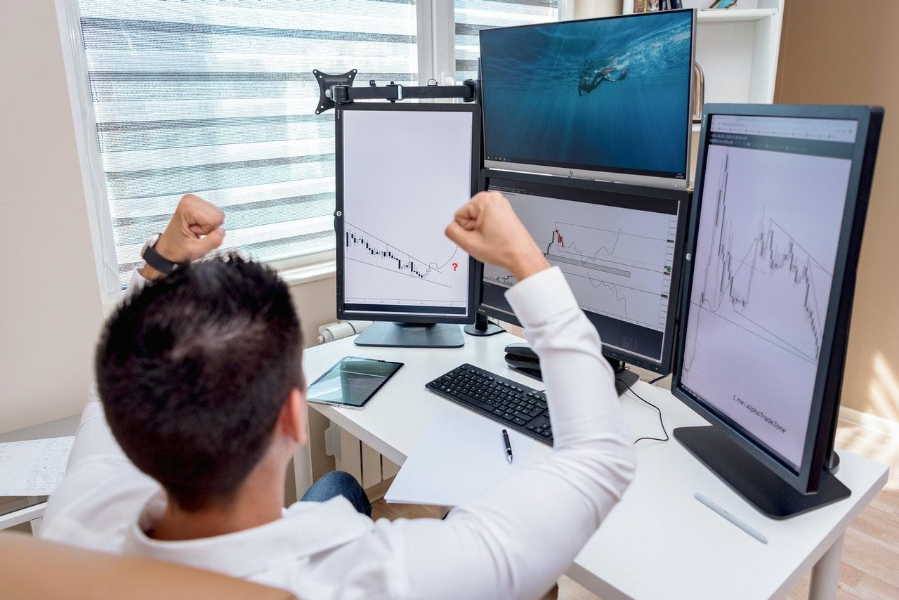 osoba z uniesionymi ramionami przed monitorami